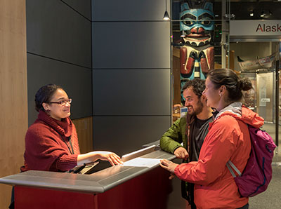 Museum Reception Area: Staff greets two visitors.