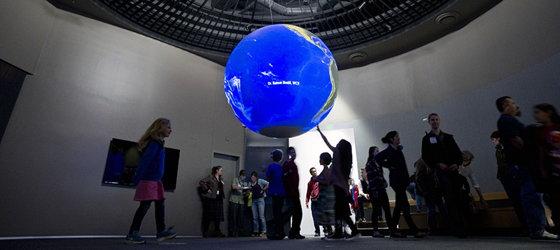Child reaches up to touch a blue globe, the Science on a Sphere exhibit.
