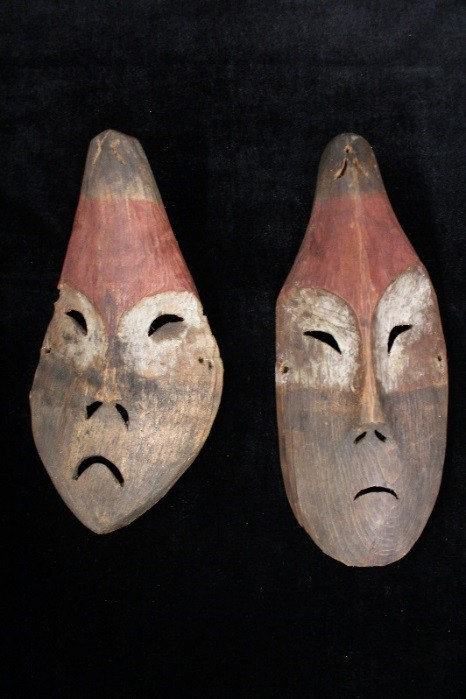 Two frowning wooden masks.