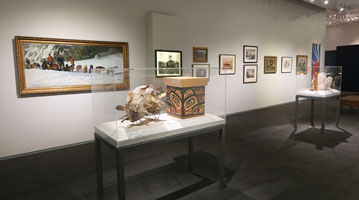 Wide shot of gallery, including a basket and paintings.