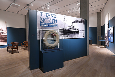 Exhibit entrance with sign Titanic of the North, blown up photo of ship, and lifesaver ring.